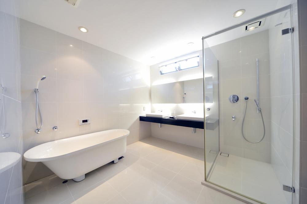 Badezimmer mit ebener Dusche und freistehender Wanne ...